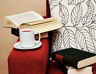 Cup of tea and some books on a red couch