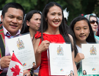 Three people at a citizenship ceremony