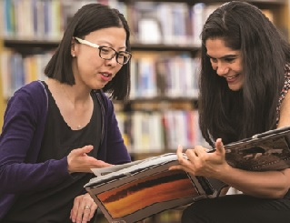 Two people looking at a book at a library