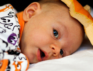 Baby in a Halloween patterned onesie