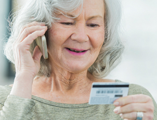 Woman talking on the phone holding a credit card