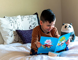 Child reading on bed